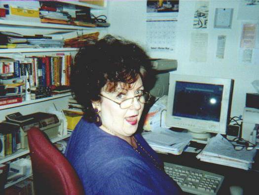 A white woman with dark curly short hair and glasses is shown seated at a computer desk with clutter bookshelves. There's an old computer with a small monitor in front of her as well as stacks of papers and an extra pair of glasses. She's wearing a blue top and is turned halfway to face the camera with a silly, joyful expression.