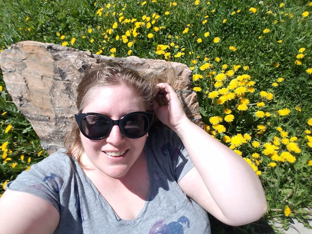 A fat woman with blonde hair, sunglasses and a gray shirt leans against a rock in a field full of dandelions.