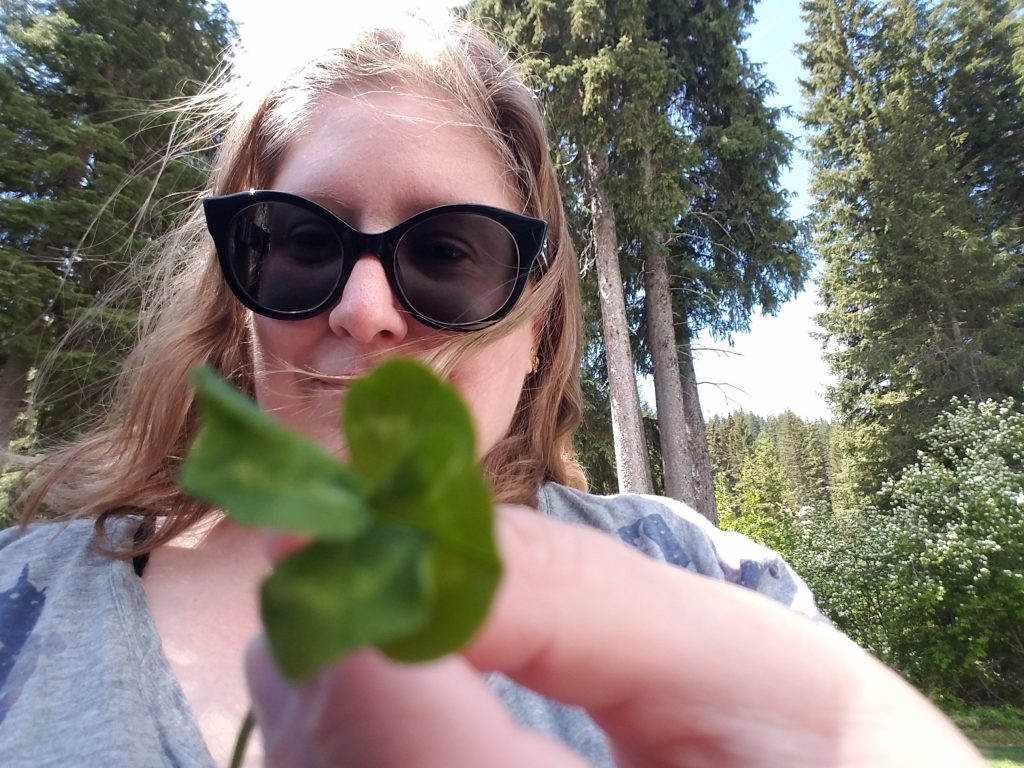 The same woman stands in front of tall pine trees and holds a four-leaf clover up to the camera, which is out of focus, darn it.