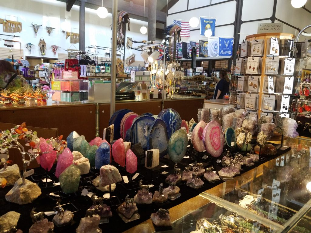 The gift shop at 50,000 Silver Dollar, which does indeed have fifty thousand silver dollar coins in its counters and on its walls. A cluttered set of counters, shelves and racks holds a variety of gemstones, figurines, cards, and jewelry.