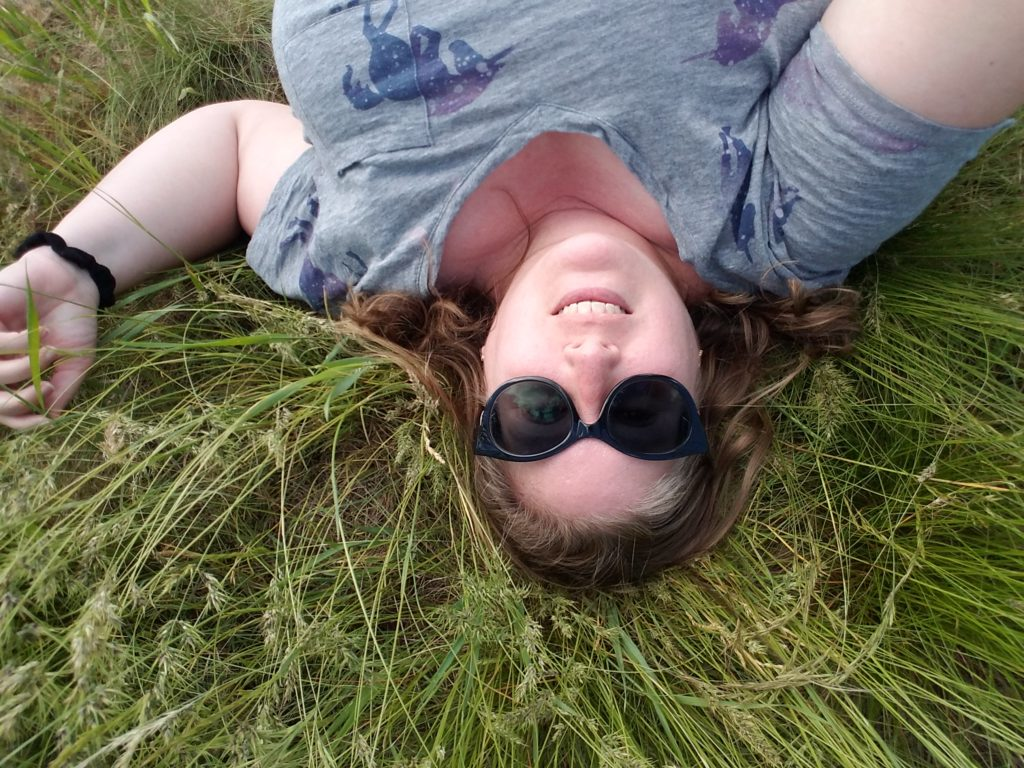A fat white woman lies on her back in tall grass.