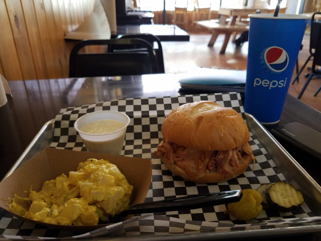 The predominant flavor of potato salad really shouldn't be black pepper, but it was a good try. Yellow potato salad, a barbecue sandwich, and a Pepsi cup are shown on a table in a restaurant with wood-paneled walls.