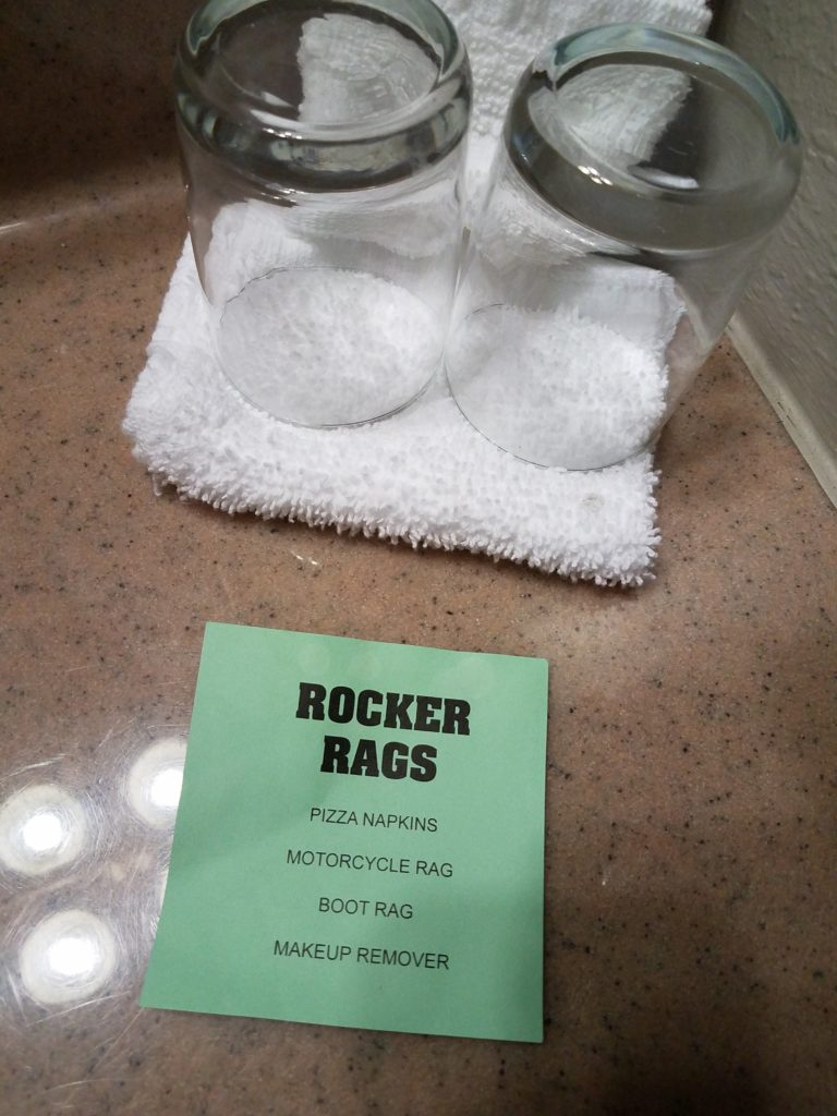 "This sign was mystifying until some Facebook friends clarified it for me. The hotel is encouraging people to use the (presumably cheaper and easier to replace) washcloths as napkins, motorcycle cloths, and so on rather than the more expensive bath towels. A green paper sign reading, ""ROCKER RAGS: Pizza napkins, motorcycle rag, boot rag, makeup remover"" is shown on a plastic hotel counter in front of a white washcloth and two drinking glasses."
