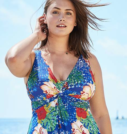 Infinite Swim: Where to Find Swimsuits in Sizes 32+  Swimwear for superfats, infinifats and over size 32 with FullBeauty. A woman with pale skin and shoulder-length brown hair stands on a beach and is shown from the waist up. She's wearing a floral one-piece swimsuit and has one hand in her hair.