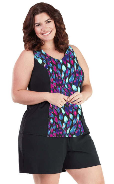 Infinite Swim: Where to Find Swimsuits in Sizes 32+  A plus size woman with pale skin and brown hair is shown on a white background, wearing black swim shorts and a colorful patterned tankini top.