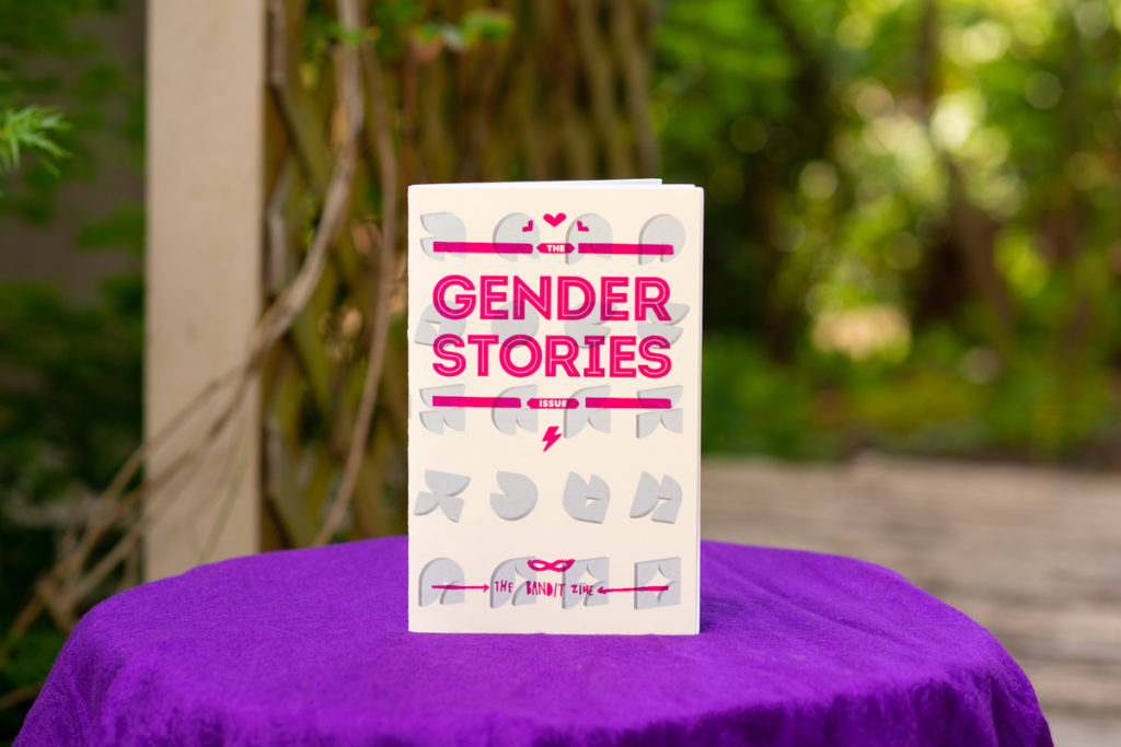 Body Positive and Fat Positive Product Photography Sessions for Products, Zines, Books, Art, Artwork, Crafts, Jewelry, Apparel, and Handmade Items  The zine Gender Stories is shown standing by itself on a purple fabric-covered stool in front of a garden arbor covered in vines.