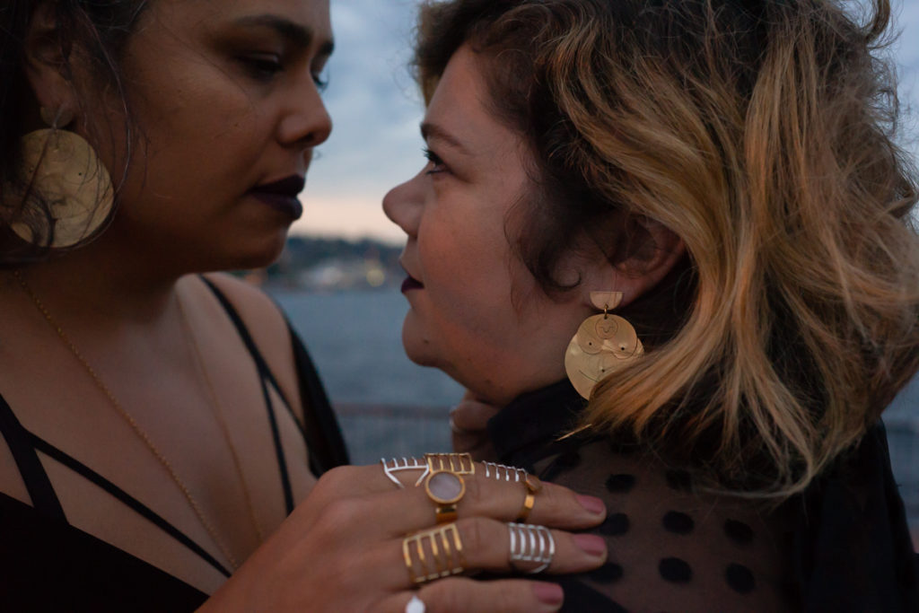 Body Positive and Fat Positive Product Photography Sessions for Products, Zines, Books, Art, Artwork, Crafts, Jewelry, Apparel, and Handmade Items  Plus-size models Croptopgoth and Adria Garcia stand close together in a sultry pose in front of Lake Union in Seattle, wearing rings and earrings made by Ohme Jewelry in gold and silver. One woman is of Native American descent and has long black hair. The other is a fat white woman with shoulder-length blonde hair.