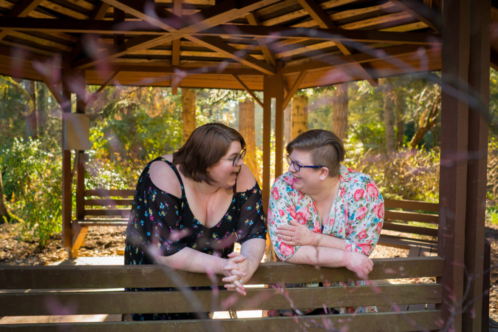 Body Positive and Fat Positive Business Branding Sessions for Podcasts, Authors, Writers, Photographers, and Dreamers  Eron Huenefeld and Amanda Underwood of the podcast Fat Face Feelings lean on a wooden railing and laugh under a large wooden gazebo on a bright day in a park with trees all around. Both are fat white women with glasses, short hair, and floral short-sleeve tops.