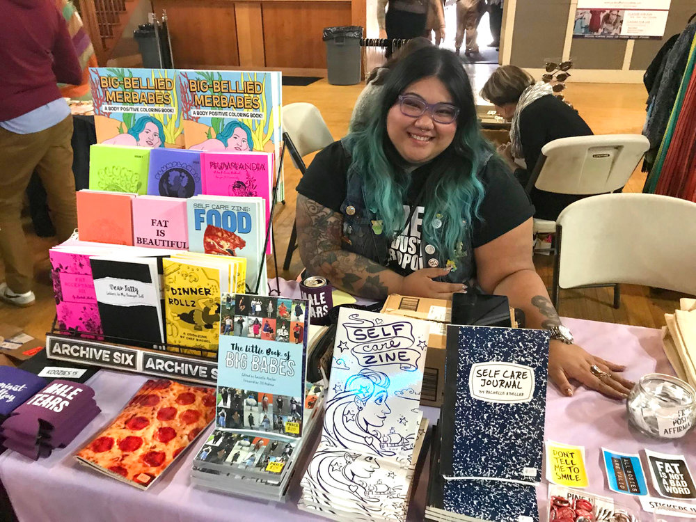 A smiling woman with brown skin, purple glasses and black and blue hair is sitting behind a table at an event with a variety of zines and stickers.