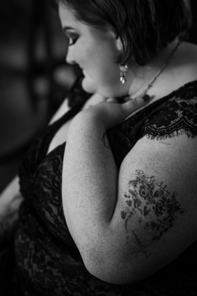 "A fat white woman wearing a black lace top, necklace and earrings, with eye makeup, and short dark hair, sits with one hand pressed to her upper chest. An owl watercolor tattoo on her upper arm is accompanied by the words ""perfectly imperfect."""