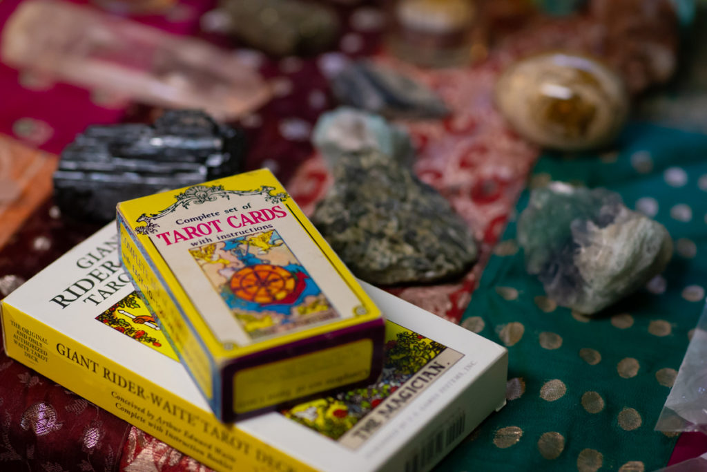 Two boxes of tarot cards and a number of crystals for crystal healing and energy work rest on a colorful fabric cloth in green, red and orange tones.
