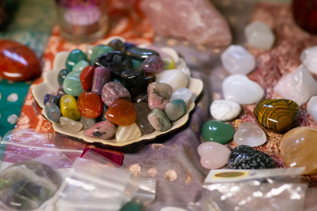 A number of colorful crystals for crystal healing and energy work rest on a colorful fabric cloth in green, red and orange tones. The stones include tiger's eyes, obsidian, aventurine and quartz hearts and tumbled pink, yellow, red, orange, purple, white, clear and green stones.