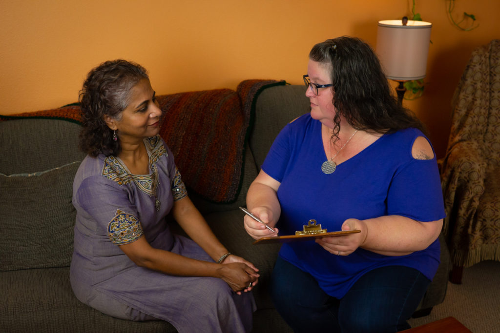A woman of Indian descent in a purple embroidered dress and a fat white woman in jeans and a dark blue top sit on a brown couch in a waiting room and discuss an appointment. The white woman holds a clipboard and pen.