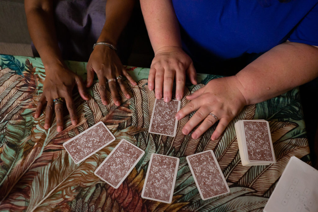 An Indian-American woman and fat white woman's hands are shown resting on a coffee table covered in a wing-pattern scarf in green, orange and brown tones. A set of tarot cards lies face-down on the table.