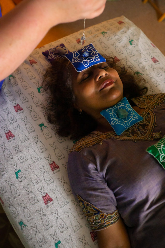 An Indian-American woman in an embroidered purple dress lies on a table covered in a cartoon rabbit-printed fabric. Chakra beanbags and gemstones lie on her forehead and chest. A white woman dangles a crystal near her face.