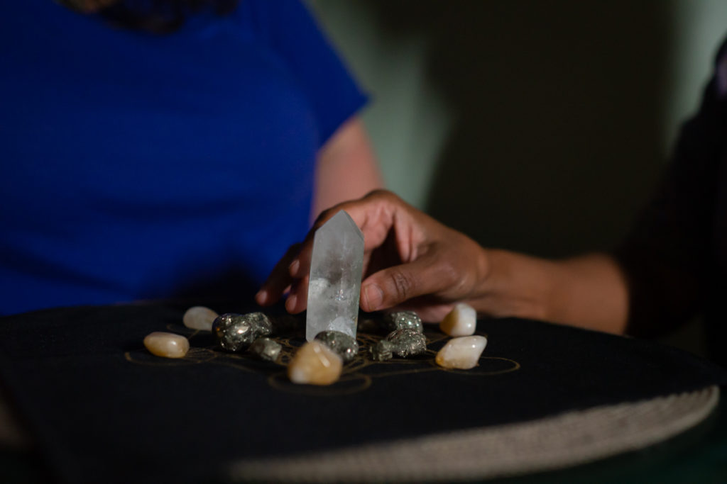 A white woman and woman of color sit at a small table; only their torsos and arms are shown. The woman of color reaches out to grasp a quartz crystal standing in the center of the table, part of a crystal healing arrangement in a golden printed mandala on a black velvet cloth.